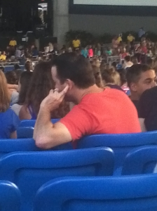 Guy plugging his ears at concert